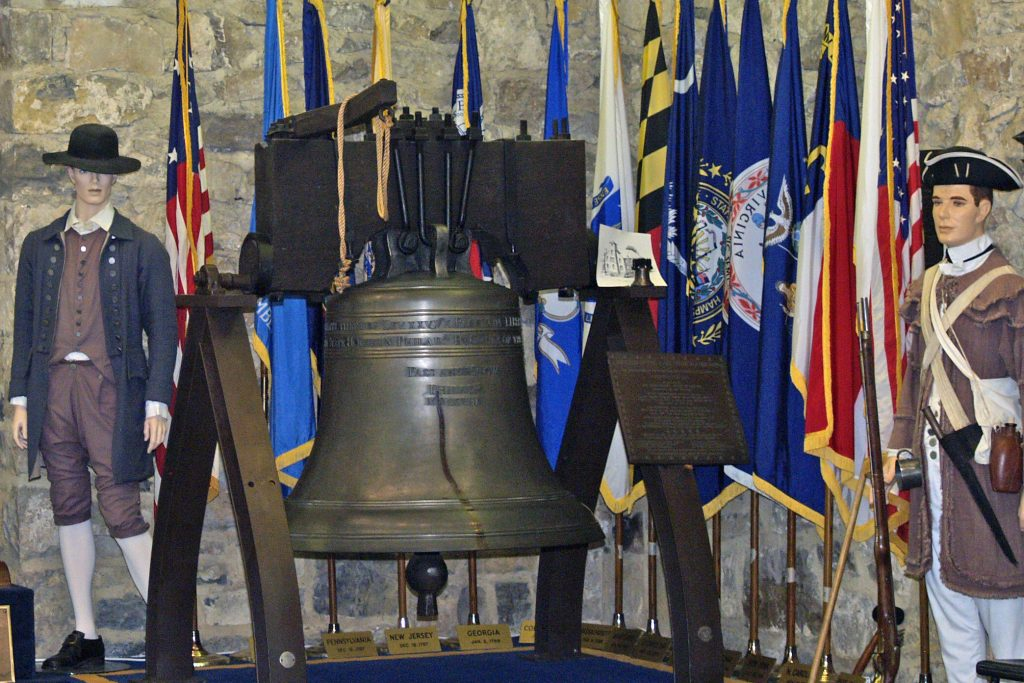 Replica Liberty Bell with flags and mannequin